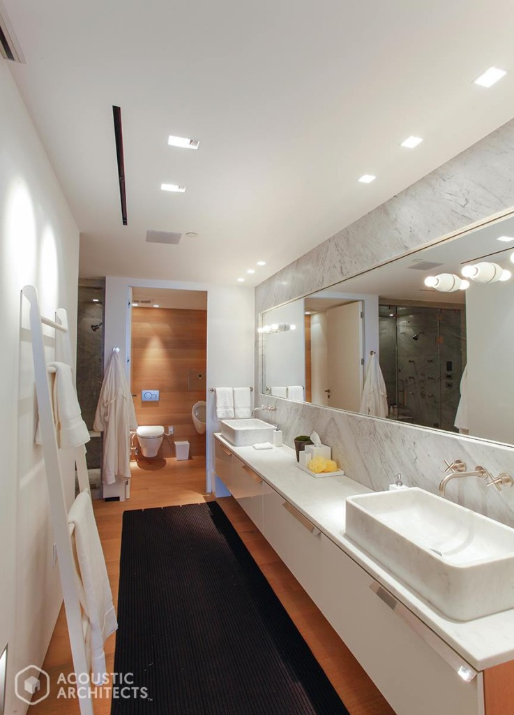 A sleek, hidden mirror TV by SÉURA raises the bar in this master bath. Room also features Sonance speakers and lighting by Lutron Electronics.